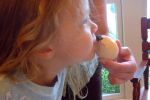 Granddaughter Irene kisses the hatching dinosaur